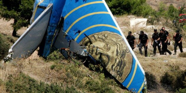 Members of the Greek police elite force walk past a tail of the Cypriot Helios airliner that crashed...