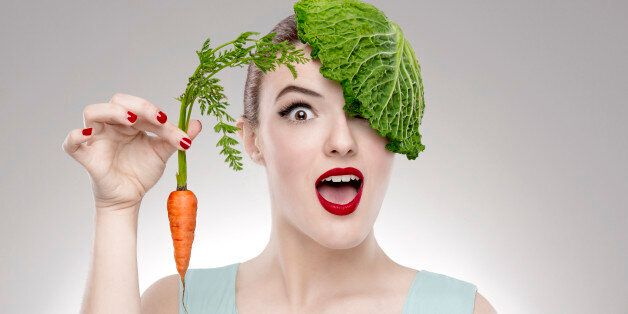 Portrait of a woman illustrating a vegan concept holding a carrots and with a cabbage on the head