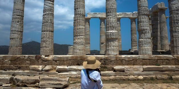 A tourist takes a picture of the temple of Poseidon at cape Sounion, 70 km soutHeast of Athens on June...