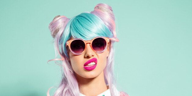 Portrait of manga style blue-pink hair girl wearing sunglasses and pink polka dot dress with collar and bow tie. Standing against turquoise background, looking at camera. Studio shot, one person.