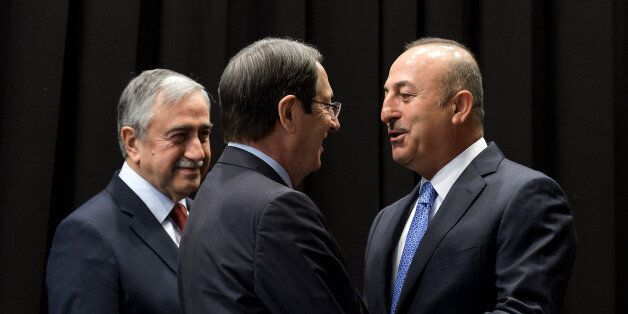 Turkish Foreign Minister Mevlut Cavusoglu (R) greets Greek Cypriot President Nicos Anastasiades (C) next...