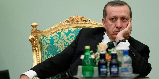 Turkey's Prime Minister Tayyip Erdogan listens to the speech of Libya's leader Muammar Gaddafi at the...