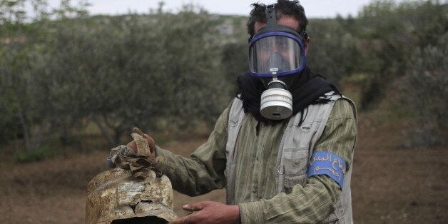 A Civil Defence member carries a damaged canister in Ibleen village from what activists said was a chlorine...