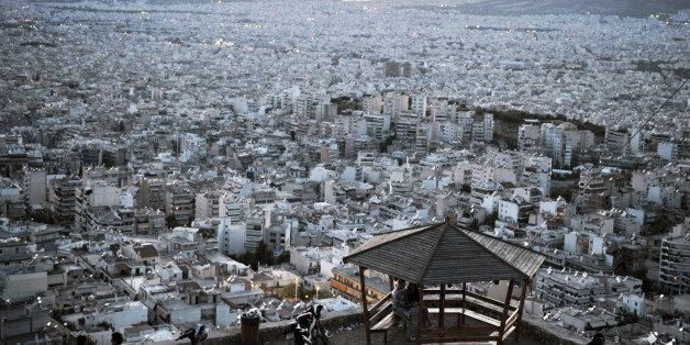 People sit on benches at a hill overlooking the city of Athens on September 15, 2013. With Greece in...