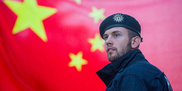 A German policeman is seen securing the area were Chinese students gathered in a display of support,...