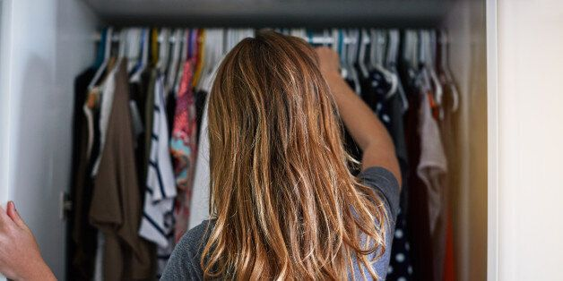 Rearview shot of a young woman standing in front of her closet choosing something to