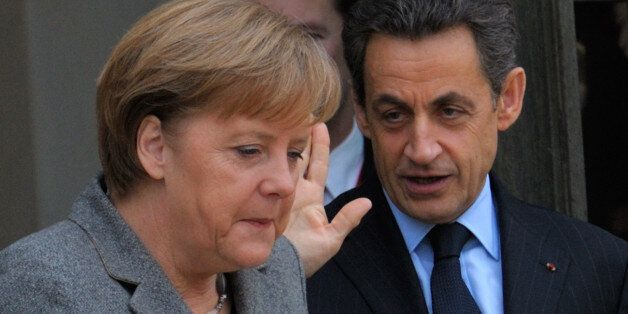 France's President Nicolas Sarkozy (R) accompanies German Chancellor Angela Merkel as she leaves the...