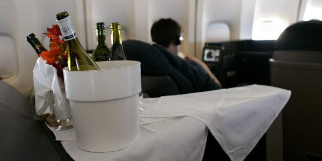 With bottles of wine in the foreground, a passenger watches a movie inside the first class cabin of a...