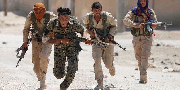 Kurdish fighters from the People's Protection Units (YPG) run across a street in Raqqa, Syria July 3,...