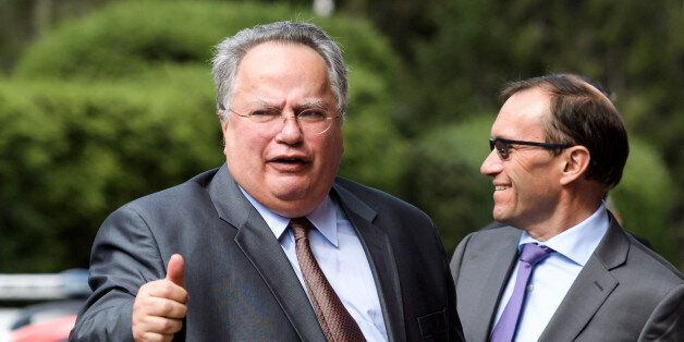 Greek Foreign Minister Nikos Kotzias (L) gives a thumb next to UN envoy Espen Barth Eide upon his arrival...