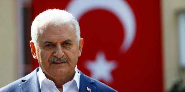 Turkish Prime Minister Binali Yildirim speaks to media next to a polling station during a referendum...