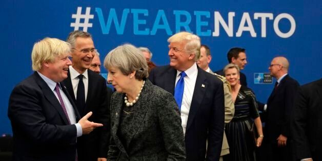 U.S. President Donald Trump (C) reacts while speaking to NATO Secretary General Jens Stoltenberg (2-L)...