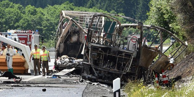 Policemen and forensic experts work at the scene where a tour bus burst into flames following a collision...