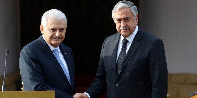 Turkish Prime Minister Binali Yildirim (L) and Turkish Cypriot leader Mustafa Akinci shake hands during...