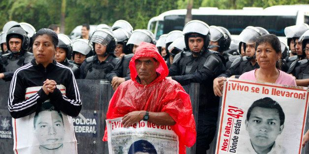 Relatives of the 43 missing students of Ayotzinapa hold their portraits in front of riot police during...