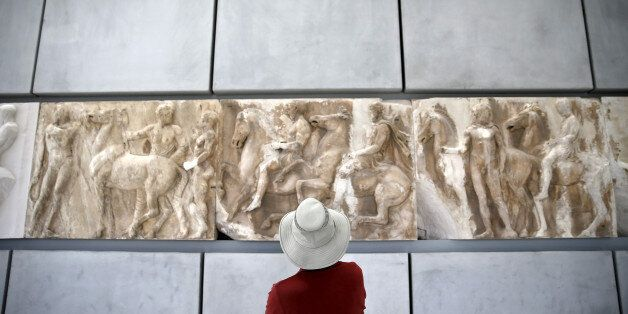 A man looks at exhibits at the Parthenon hall of the Acropolis museum in Athens, Greece, May 18, 2015....