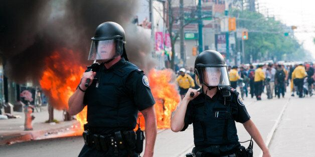 Toronto, Canada - June 26, 2010: A male and female police officer standing in front of a burning police...