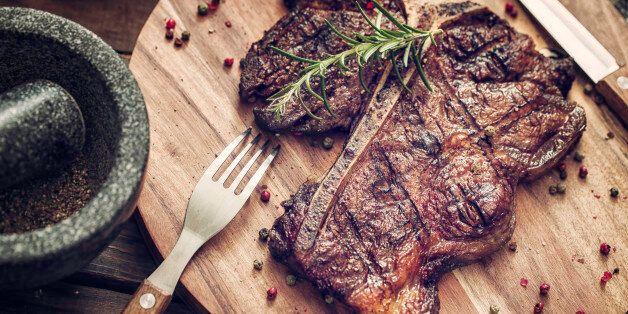 Delicious T-Bone Steak Medium Roasted with Herbs and Pepper. The steak is on a wooden plate served with...