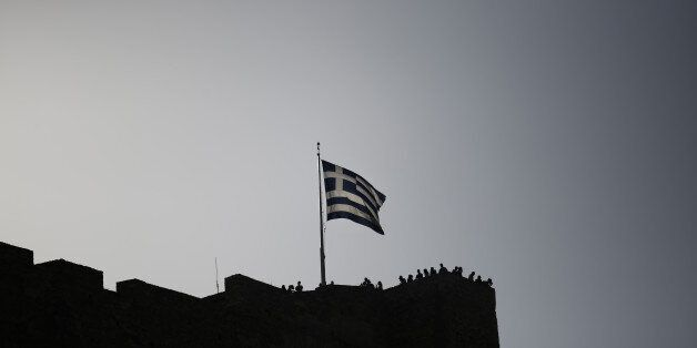 A Greek national flag flies from the top of the Acropolis hill above visiting tourists in Athens, Greece,...