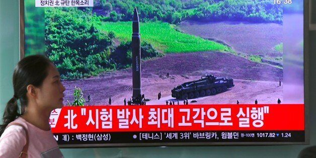 A woman walks past a television screen showing a picture of North Korea's test launch of an intercontinental...