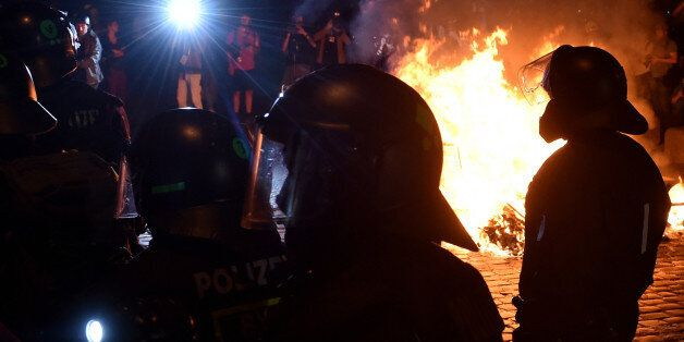 Police officers walk in front of a fire after the 'Welcome to Hell' rally against the G20 summit in Hamburg,...
