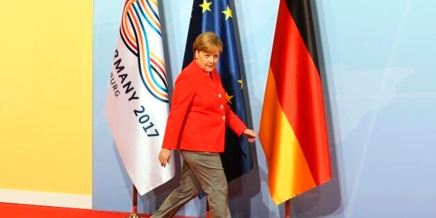 German Chancellor Angela Merkel walks past flags as she arrives before greeting heads of State at the...