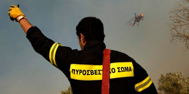 A firefighter gestures as a fire-fighting helicopter flies in the background during a forest fire at...