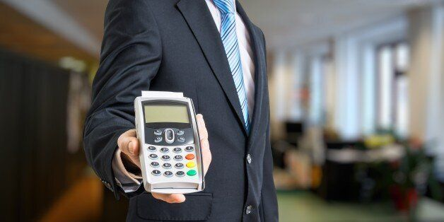 Businessman is offering payment terminal for paying with credit card in