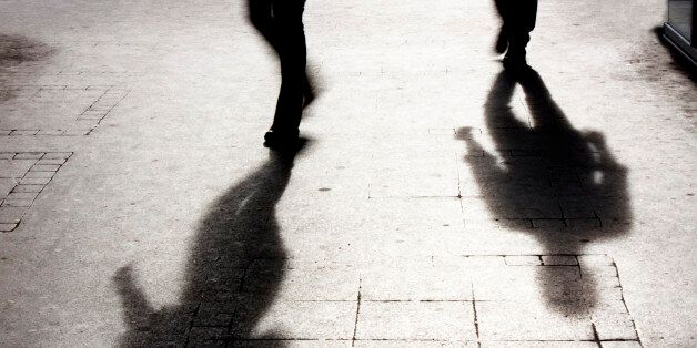 Shadow of two person on pattered sidewalk in black and