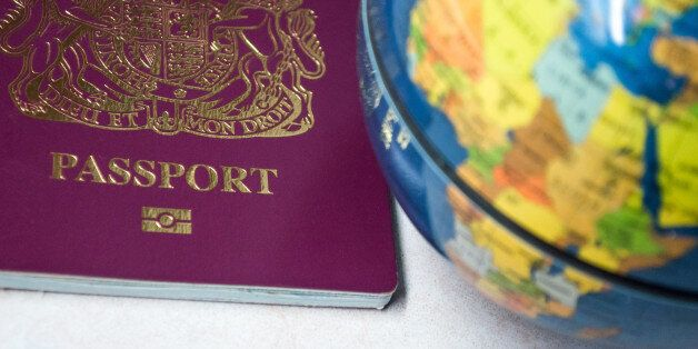 The bottom half of a British passport, next to a globe.