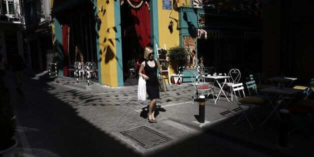 A pedestrian carries shopping bags in the Psyri neighbourhood in Athens, Greece, on Tuesday, June 13,...