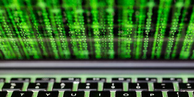 Laptop screen and keyboard with green binary matrix code closeup cybersecurity