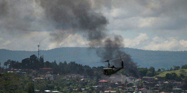 A helicopter flies through smoke billowing from houses after aerial bombings by Philippine Airforce planes...