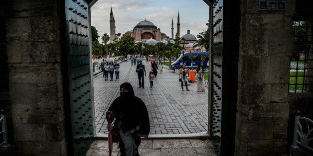 TOPSHOT - A woman walks through a gate of the Blue mosque square before breaking time as Hagia Sofia...