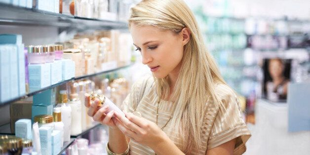 A young woman reads the information on a bottle of