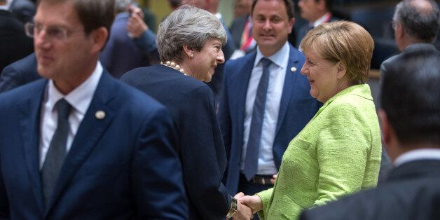 Theresa May, U.K. prime minister, center left, shakes hands with Angela Merkel, Germany's chancellor,...