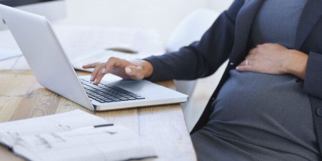 Cropped image of a pregnant businesswoman working on her laptop in the