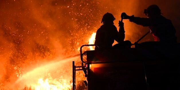Firefighters try to extinguish a wildfire in Colmeal, near Gois on the night of June 21, 2017. The huge...
