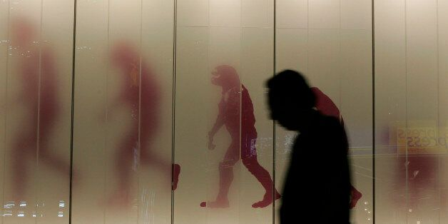A man walks past a sign showing the evolution of man in a business district in downtown Tokyo November...