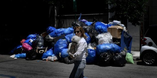 TOPSHOT - A woman holding her dog walks past a pile of garbage in central Athens on June 22, 2017, as...