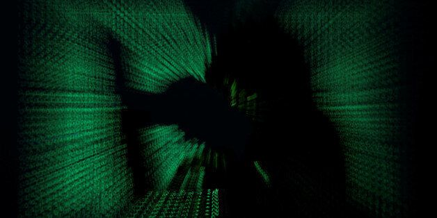 A hooded man holds laptop computer as cyber code is projected on him in this illustration picture taken...