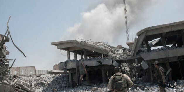 MOSUL, IRAQ - JUNE 17: Iraqi Army soldiers in a destroyed street after an Iraqi forces airstrike targeted...