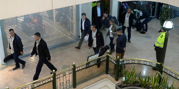 Colombian President Juan Manuel Santos (C) tours a shopping center, following an explosion which, according...
