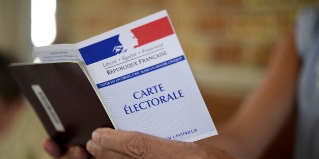 A woman holds a electoral card at a polling station in Carhaix-Plouguer, western France, during the second...