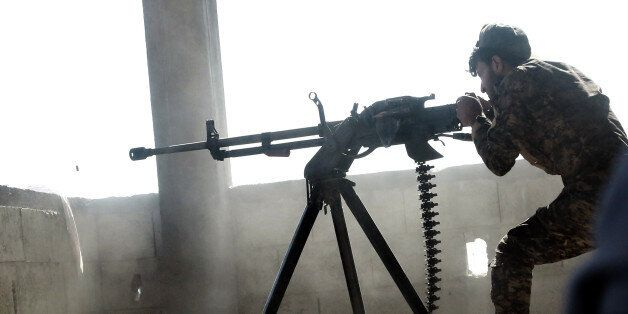TOPSHOT - A member of the Kurdish People's Protection Units (YPG) fires a machine gun in the Syrian city...