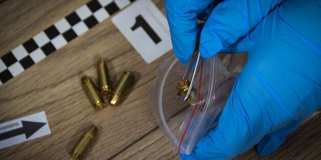 Forensic experts collects evidence from the crime scene. Bullets packed in a bag with a pair of