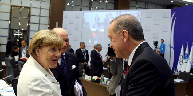 Turkey's President Tayyip Erdogan (R) chats with German Chancellor Angela Merkel prior to a working session...