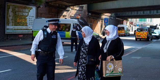A police officer speaks to local residents at a police cordon, close to the scene of a van attack in...