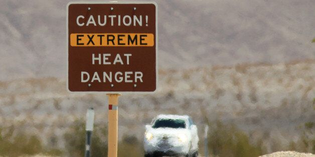 DEATH VALLEY NATIONAL PARK, CA JULY 14: Heat waves rise near a heat danger warning sign on the eve of...