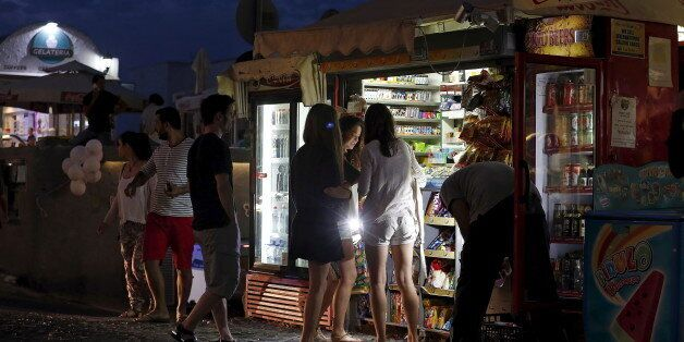 Tourists buy water from a vendor on the Greek island of Santorini, Greece, July 1, 2015. Greece's last-minute...
